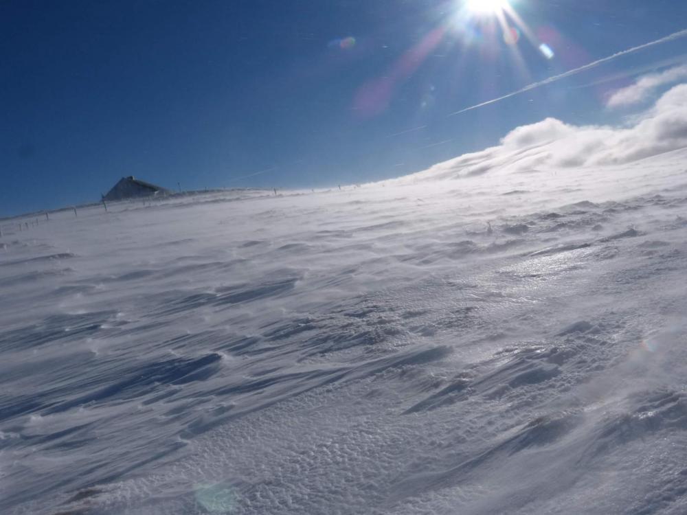des volutes de neige se soulèvent sous l' effet du vent, et une barre nuageuse s' approche sur la droite